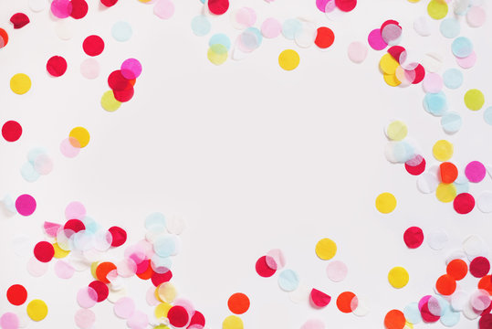 Colorful paper confetti scattered around a white background leaving a blank space empty in the center