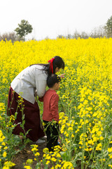 Mother and son in the spring rapeseed field