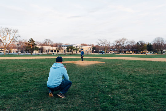 father and son on a baseball field playing catch