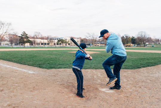 Dad showing baseball bat swinging tricks to his son