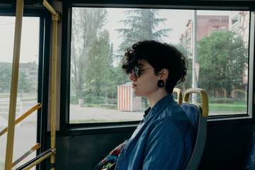 Portrait of a female model with sunglasses traveling by bus