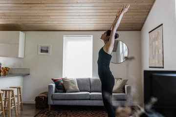 woman practices yoga in modern home living room