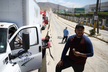 Truck drivers eat an ice cream as they wait in a long queue for border customs control to cross into the U.S., in Tijuana