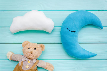 Baby care concept with moon pillow, clouds, teddy bear and toy for sleep of newborn on mint green...