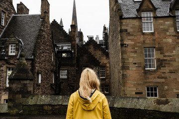 blonde woman backwards wearing a yellow raincoat looking to a medieval housing