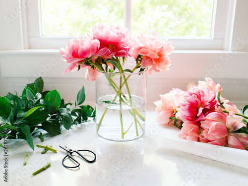 Pink peonies being arranged in glass vase