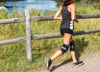 Female cross country runner racing with two knee braces