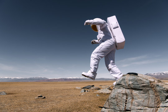 Astronaut jumping down from mountain
