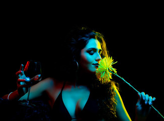 Beautiful, curly haired brunette holding a wine glass with red wine in one hand and a yellow dandelion that she is smelling in the other while being covered in red, blue and yellow studio lights.