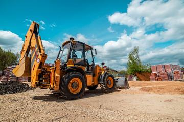 Yellow bulldozer excavator on the construction site working machine