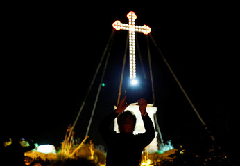 A man takes pictures with a tablet near Laferla Cross during a Seven Churches Visitation pilgrimage as part of Holy Week activities on Maundy Thursday in Malta
