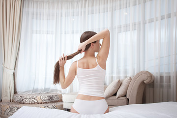 Young pretty woman stretching and do morning work-out on big bed at home. Woman in white Panties and T-shirt. Smiling and happy person in hotel room.