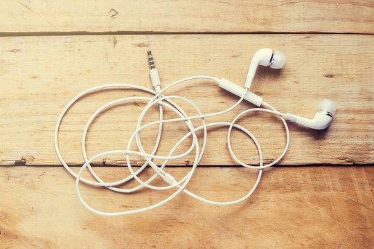 Modern white earphone, white in ear headphone on wooden table.
