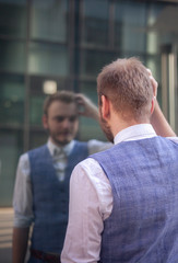 one young businessman looking at himself in a window mirror.