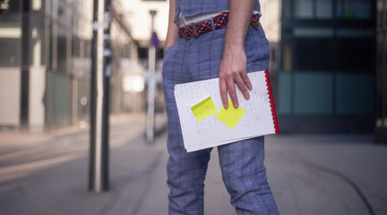 close-up of man holding a notebook with sticky notes on them.