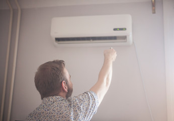 one young man turning on his air conditioner.