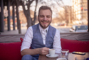 one young smiling man sitting in a coffee shop.