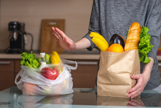 Woman chooses a paper bag with food and refuses to use plastic. Environmental protection and the abandonment of plastic