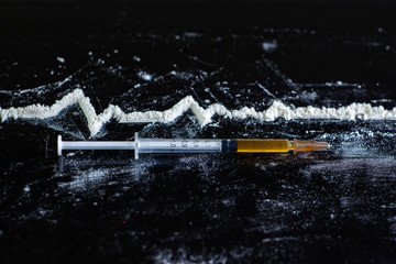 clinical picture of a drug overdose: a syringe of heroin next to an image of the cardiogram