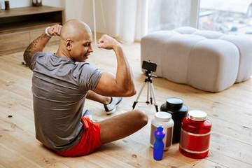 Bald bodybuilder making photo using smartphone and phone stand