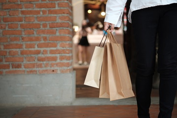 Young woman holding sale shopping bags. consumerism lifestyle concept in the shopping mall