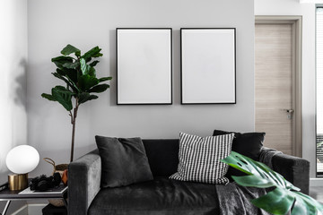 Cozy Living room corner with dark gray velvet fabric sofa , artificial plants and empty picture frame installing on the wall / cozy interior concept /space for advertising /scandinavian style interior