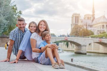 Happy family having fun near Notre-Dame cathedral in Paris. Tourists enjoying their vacation in France.
