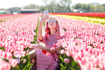 Young woman wear sunglasses make selfie in tulips flower field in sunny spring day