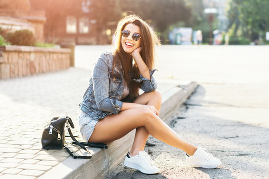 Pretty young smiling brunette girl relaxing outdoor on the street.