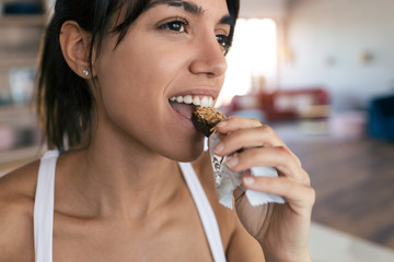 Sporty young woman eating muesli snack at home.