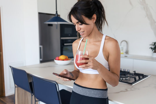Sporty young woman using her mobile phone while drinking strawberry smoothie in the kitchen at home.