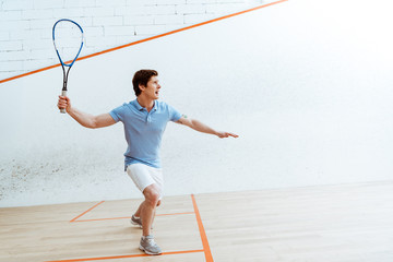 Emotional sportsman in blue polo shirt playing squash in four-walled court Wall mural