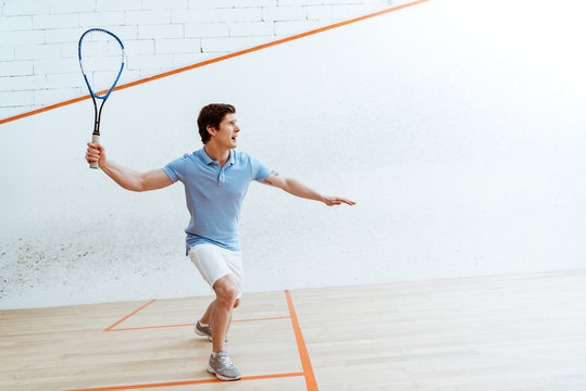 Emotional sportsman in blue polo shirt playing squash in four-walled court