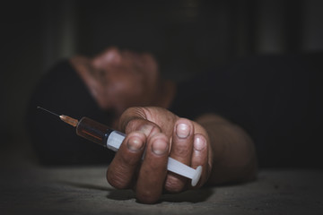 Man lying on the floor  after overdosing on opioid drugs and holding the syringe in his hand, The concept of drug overdose.