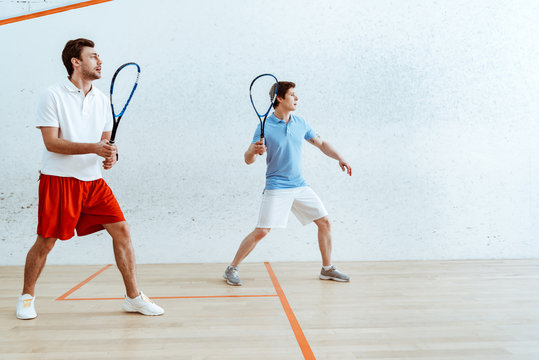 Full length view of two sportsmen playing squash in four-walled court
