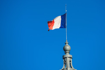 French flag flies on top of an historical building