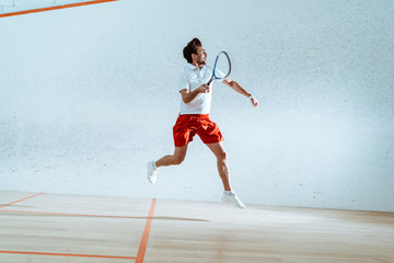 Full length view of sportsman with racket running while playing squash