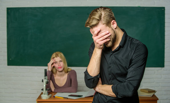 He is so shy. Male student with examiner at examination. High school student saying lesson. Handsome man standing in classroom with teacher. University or college student covering face