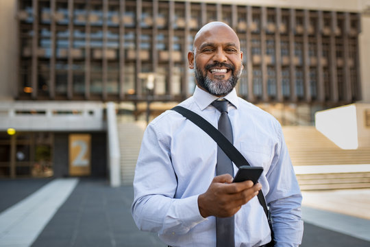 Happy mature businessman using phone