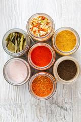 Kolorowe przyprawy  i suszone warzywa w słoikach. Mieszanki przypraw stojące na kuchennym blacie.
