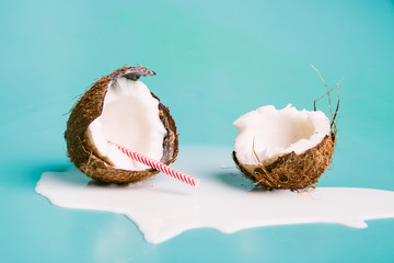 Coconut milk with a straw on turquoise background. Half of coconut on blue background. Tropical fruit concept.