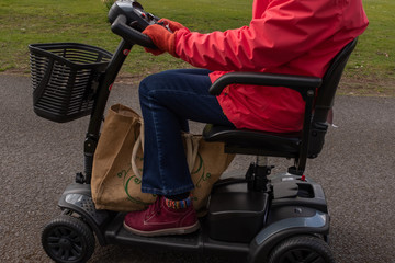 A side on shot of an elderly lady in a red coat enjoying the freedom of an electric mobility scooter, from the shoulders down Wall mural