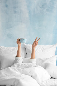 Young woman with cup of hot beverage showing victory gesture in bed