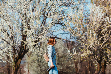 Girl photographer enjoying spring day in nature with a blooming cherry tree.