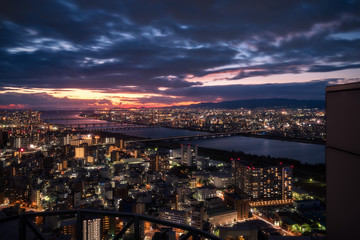 Magic Sunset View over Osaka City with bridges over Yodo River from the top of the Umeda Sky Building in Kasai Region, Japan.