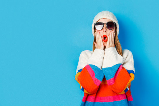A young girl with a surprised face in a white hat, glasses and a sweater on a blue background. The concept of winter, mililealy, hippster.