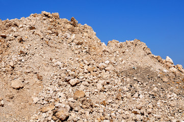 heap of gravel in front of blue sky