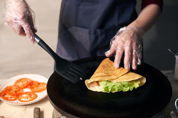 Chef in gloves making crepe on hot round portable cooktop. Skillful hands with spatula in final stage of cooking crepe stuffed with vegetables. Tomato slices on background. Healthy food. Close up view