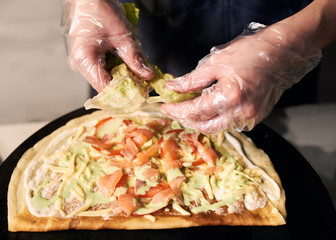 Chef's cropped hands in disposable gloves tearing green leaves of lettuce on round thin baked base for pizza cooking. Chopped pieces of fish, tomato, grated cheese on crepe on black tray. Close up.