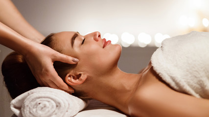 Young woman receiving professional head massage at spa